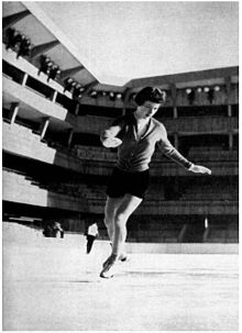 A woman does a spiral on skates in a stadium.