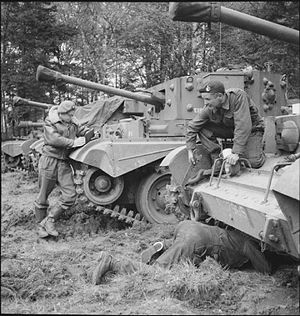 Carl Giles - The Express cartoonist Giles sketches as Cromwell tank crewmen work on their vehicles, 1 May 1945.
