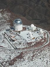 Looking down from the sky at a series of buildings and a large domed telescope building that dwarfs the others. An access road encircles the complex.