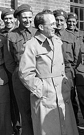 Tommy Douglas stands in front of a group of men in military uniform.
