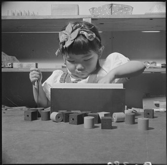 A young internee playing in a nursery school Topaz, Utah. Educational games are part of the prescribed course of study in the nursery schools at . . . - NARA - 537016.tif