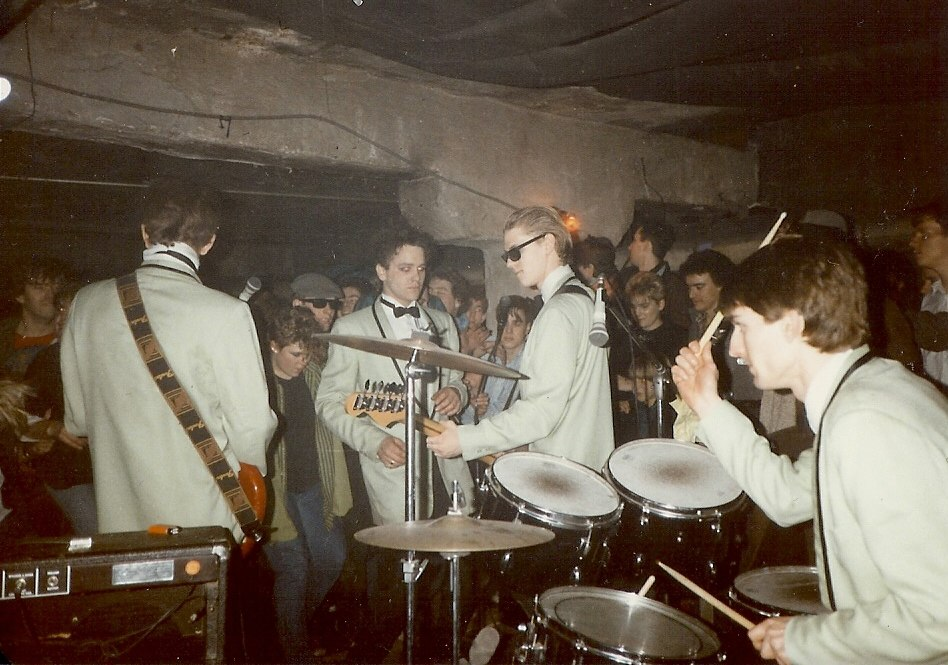 A rock band, the U-Men, playing onstage in a small venue with low ceilings. The band members are wearing matching grey suits and bow-ties.