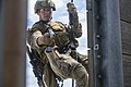U.S. Marine Corps Cpl. Jacob Carpenter, a reconnaissance Marine assigned to Maritime Raid Force, 31st Marine Expeditionary Unit, simulates attacking a target through a window while rappelling down a rappel tower on Camp Hansen in Okinawa, Japan.jpg
