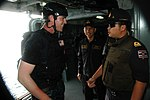 U.S. Navy Lt. j.g. Taylor Hamilton, left, a force protection officer and a visit, board, search and seizure team leader assigned to the guided missile destroyer USS Curtis Wilbur (DDG 54), greets a Royal Thai 130610-N-AX577-031.jpg