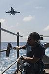 U.S. Navy Seaman Lyndon Cobin paints a handrail as an F-A-18 Hornet aircraft flies overhead aboard the aircraft carrier USS George H.W. Bush (CVN 77) in the Atlantic Ocean Aug. 7, 2013 130807-N-MW819-084.jpg