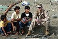 US Navy 050111-N-9885M-177 Marine Capt. Jamey Stover, assigned to the 15th Marine Expeditionary Unit (MEU), sits down with local Indonesian children as Sailors and Marines offload supplies from a Landing Craft Air Cushion (LCAC.jpg