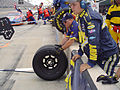 US Navy 050723-N-7321H-002 Honorary Pit Crew Member, Navy Career Counselor 2nd Class Thomas Burke, keeps a replaced tire from rolling back into the pit lane during a pit stop at the NASCAR Busch Series Salute to the Troops 250.jpg