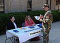 US Navy 051031-N-1132S-001 Chief Alan Reling, assigned to Naval Mobile Construction Battalion Seven (NMCB-7), speaks with representatives Lynn Spencer and Michelle Hauptmann at a job fair.jpg