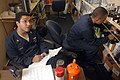 US Navy 061025-N-1332Y-174 Storekeeper 3rd Class Freddy Cruz from New York City, and Aviation Support Equipment Technician 3rd Class Daniel Brown from Los Angeles, complete a customer's paint order.jpg