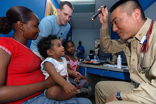 US Navy 070706-N-8704K-090 Lt. Cmdr. Harry Ko, U.S. Public Health Service attached to Military Sealift Command hospital ship USNS Comfort (T-AH 20), provides medical care at the Paul Brown Arena