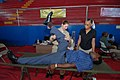 US Navy 070706-N-8704K-101 Lt. Gwen Smith, attached to Military Sealift Command hospital ship USNS Comfort (T-AH 20), performs physical therapy with the help of translator Zoela Armstrong at the Paul Brown Arena.jpg
