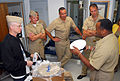 US Navy 070716-N-0962S-183 Command Master Chief Larry Darnell, Navy Exchange Service Command, explains to the four Sailors of the Year (SOYs) how to change the material on the white combination cover to wear with their new khak.jpg