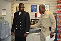 US Navy 070816-N-8102J-008 Chief petty officer (CPO) selectee, Gas Turbine System Electrical 1st Class Tremane Mason, tries on his new chief's uniform with the help from his sponsor, Senior Chief Sonar Technician Surface Brian.jpg