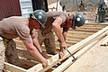 US Navy 080606-N-9623R-016 Utilitiesman 1st Class Todd Feltus, left, and Builder 1st Class Jeffrey Hood work to construct floors and trusses for South West Asian huts.jpg