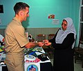 US Navy 090220-N-4774B-046 Lt. j.g. Jarrod Johnson hands a ship's coin to the head of staff of the Kuda Kudhin ge Hiya neglected children's home in Villingili.jpg