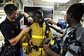 US Navy 090611-N-5242D-231 Damage Controlman 1st Class James Harry, Damage Controlman Fireman Jason King and Djiboutian Navy Sublieutenant Moussa Hanfare help Djiboutian Navy Cpl. Abdoullauder Issa don a fire-fighting ensemble.jpg