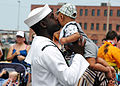 US Navy 090805-N-5292M-987 Information Systems Technician 1st Class Leonard Moore holds his six-month-old son during a homecoming celebration for the guided-missile frigate USS Kauffman (FFG 59).jpg