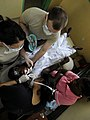 US Navy 100317-N-7948C-082 Air Force Capt. Eirleen Hyun performs a dental examination on a Ghanaian patient as dental assistant Air Force Sgt. Michael Wilde and Air Force Airman 1st Class Sable Price assists her.jpg