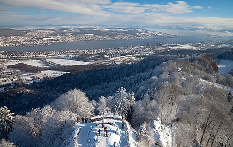 """View from the top of the telecommunications tower at Uetliberg, Zurich, Switzerland. On the foreground: the observation deck at Uto Kulm, Uetliberg. On center: Lake Zurich and the """"Golden Mile"""" of Zurich. Background, right: the alps of canton Glarus."""