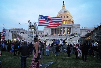 Pro-Trump rioters stormed the U.S. Capitol Building on January 6 United States Capitol outside protesters with US flag 20210106.jpg