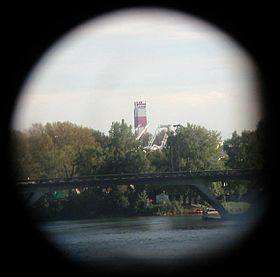 La cheminée de l'usine vue du centre-ville vue des jumelles touristiques installées sur le Pont-Neuf, d'une distance d'environ 3,8km.