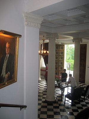 Friends of the Vermont State House - A guide at the State House greets tourists in the Entrance Hall. A portrait of Warren Robinson Austin, Vermont born U.S. Ambassador to the United Nations, hangs in the stairwell to the left.