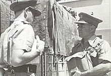 Two men in military uniform conversing next to a wooden structure. The man on the left is slightly side on with his back to the camera, while the man on the right is slightly shorter and holding a bag.
