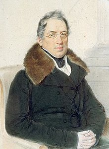 A man with thin grey hair sits in a chair, hands folded on his lap. He is wearing a grey coat with a brown fur collar.
