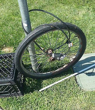 Bicycle theft - A single bicycle wheel remains locked to a pole of a stop sign at River Park Shopping Center's parking lot in Fresno, California, after the bike has apparently been unbolted from the wheel and carried away.