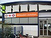 "A white-panelled building with a rectangular, orange sign reading ""Willesdon Junction"" in white letters all under a light blue sky"