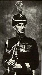 Formal portrait of man in dark-coloured dress uniform and headgear with braid and medals