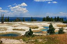 Diverse piscine di acqua blu in bacino di roccia color cenere.
