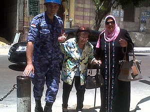 Egyptian presidential election, 2014 - Soldier helps an elderly woman to reach the polling station in Alexandria – 27 May 2014