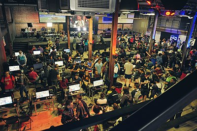 Overhead shot of a room full of people. In the foreground, several monitors are set up on tables and people are competing around each one. In the background, a light and camera setup focuses on a featured match, which is broadcast on a screen that audience members are watching.