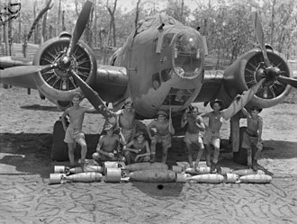 Light bomber - 1943. A twin-engine Lockheed Hudson of No. 2 Squadron RAAF. Its crew and ground staff pose for the photographer, prior to loading the Hudson with its bomb load in the foreground.