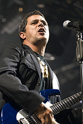 A man with a black jacket, black shirt with gold accents, singing in a microphone with his hand on a blue guitar.