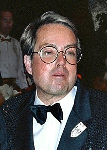 The photograph of a bespectacled man wearing a tuxedo with a white and black pocket square in his left chest pocket.
