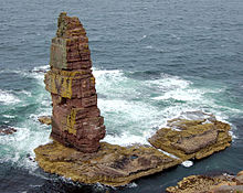 A tall sea stack stands on a wave-lashed rocky platform of rocks.