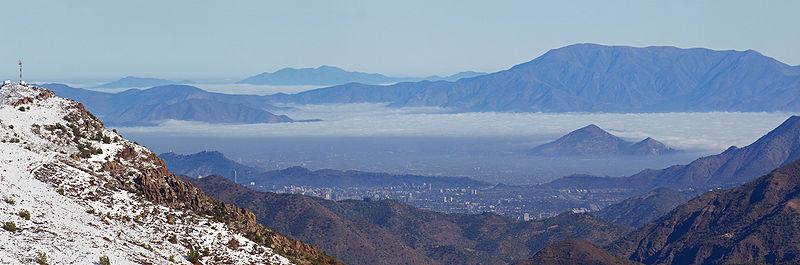 Vista panorámica de Santiago, parcialmente cubierto por el esmog y las nubes y rodeado por Los Andes y la Cordillera de la Costa.