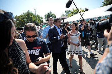 Yang speaks with a media reporter. There are several people and camera crew around.