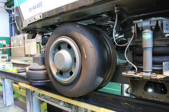 Rubber-tyred metro - The bogie of an MP 05, showing the flanged steel wheel inside the rubber tyred one, as well as the vertical contact shoe on top of the steel rail.