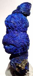 A vertical cluster of four deep blue azurite rosettes mounted on small white base