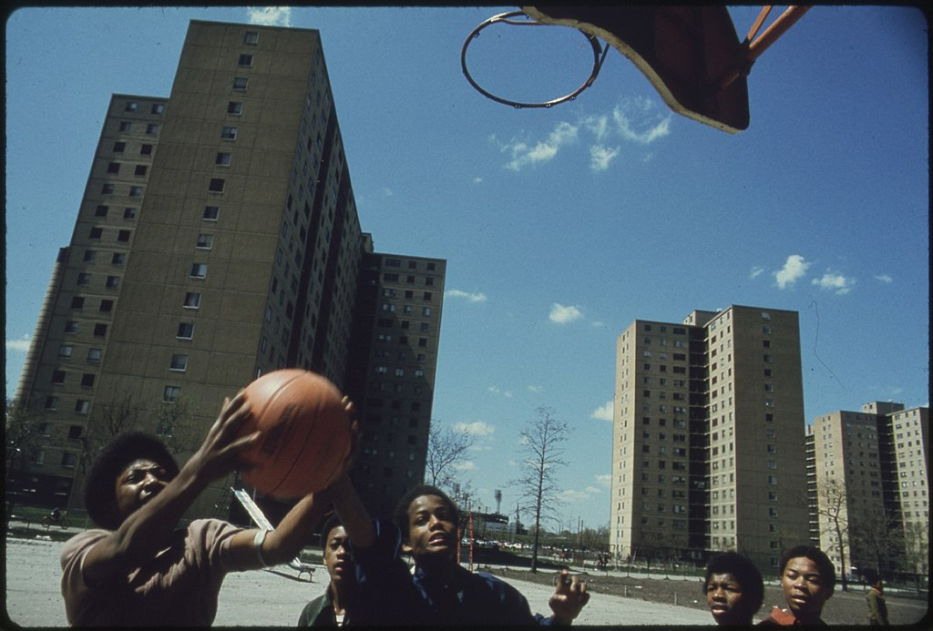 BLACK YOUTHS PLAY BASKETBALL AT STATEWAY GARDENS' HIGHRISE HOUSING PROJECT ON CHICAGO'S SOUTH SIDE. THE COMPLEX HAS... - NARA - 556162