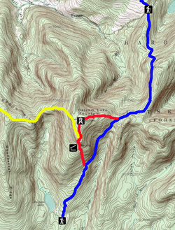A topographic map of Balsam Lake Mountain with brown contour lines on a green and white background. Red, yellow and blue lines indicate the trails, with black-and-white pictograms denoting the fire tower, lean-to and trailhead facilities