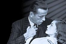 Black-and-white image of a man and a woman, seen from mid-chest up, their faces in profile, gazing into each other's eyes. He embraces her in a dip with his right arm and holds her right hand to his chest with his left hand, he wears a pin-striped suit and a dark tie. She wears a white top, on the left, the background is black; on the right, it is lighter, with a series of diagonal shadows descending from the upper corner.