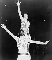 A basketball player, with the number 42 on his short-sleeved uniform, leaping high into the air with his right hand stretched upward.  He is being guarded by another player with the number 24 on his shirt.