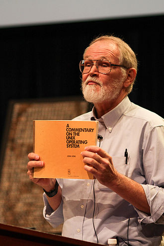 Lions' Commentary on UNIX 6th Edition, with Source Code - Brian Kernighan holding a copy of Lions's Commentary