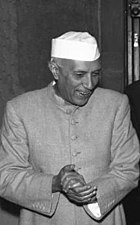 A dark-complected man wearing a gray, buttoned-up jacket and a white hat stands with his hands clasped in front of him