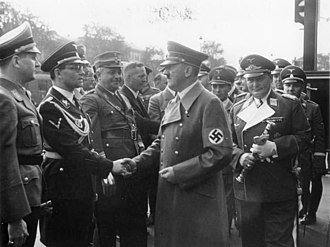 Baldur von Schirach - Schirach (extreme left) watches as Hitler greets his Chancellery chief Philipp Bouhler in Munich 1938.