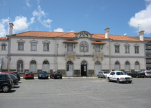 "Railway station. Two-story white building with terra-cotta roof. ""Caldas da Rainha"" written atop center of façade."